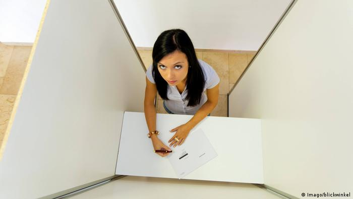 Junge Frau in Wahlkabine (Imago/blickwinkel)