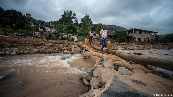 Children carry water canisters across a makeshift bridge made of logs