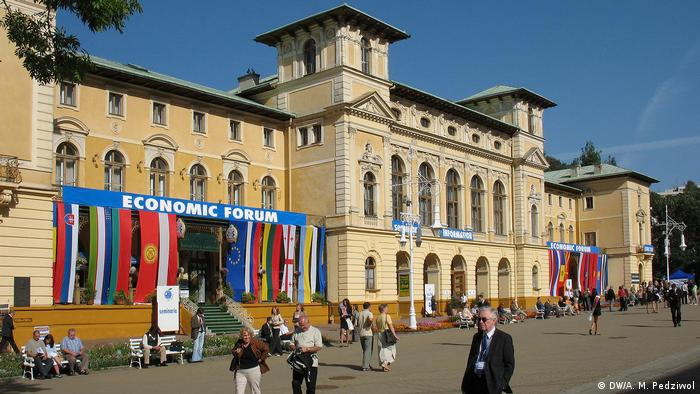 The buil   ding where the Economic Forum is being held. European country flags can be seen hanging from the buidling.