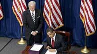 Vice President Joe Biden looks on as President Barack Obama signs the economic stimulus bill