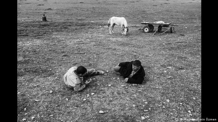 A black-and-white photo shows two men lying on the ground, with one checking his phone while horse and card stand in the background (Foto: Magnum/Emin Özmen)