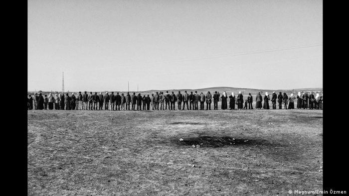A human chain made of Kurds stands in a barren landscape (Foto: Magnum/Emin Özmen)