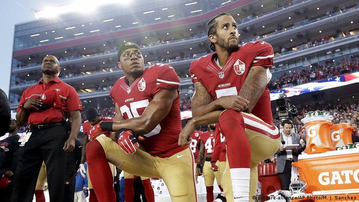 San Franciso 49ers Eric Reid and Colin Kaepernic take a knee during a national anthem performance before a football game in a stadium (picture-alliance/AP Photo/M. J. Sanchez)