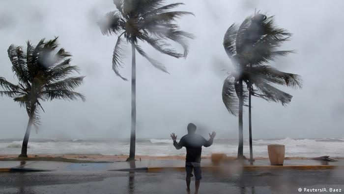 A man reacts in the winds and rain