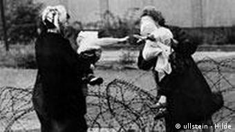 Two mothers holding up their children, who are reaching out their hands to each over the barbed wire that was the first Wall