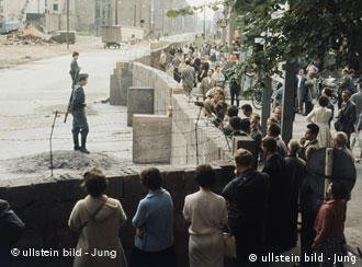 West Berliners gazing at East German border guards across the newly built Wall