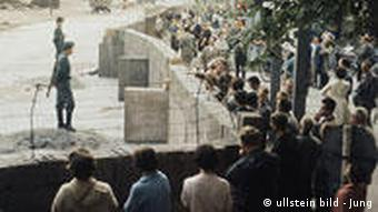 Guards on the East side of the Wall in 1961; people on the West side trying to catch a glimpse