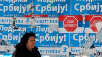 A woman in Kosovo walks past pro-Serbia posters