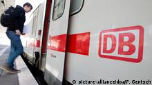 A passenger boards a Deutsche Bahn train