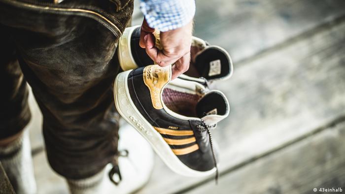 Man in lederhosen holding adidas shoes (43einhalb)