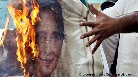 Protestors burn a picture of Suu Kyi