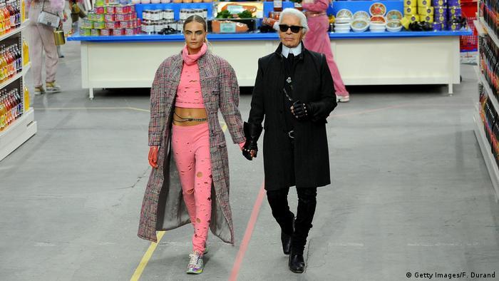 Modedesigner Karl Lagerfeld schreitet bei der Pariser Modewoche 2014 an der Hand von Model Cara Delevingne in Jogginghosen über den Laufsteg (Foto: Getty Images/F. Durand)