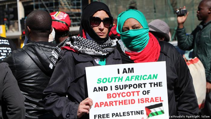 Women in South Africa hold up a sign expressing support for the BDS movement.