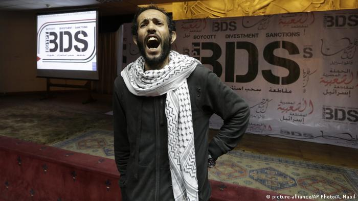 An Egyptian shouts anti-Israeli slogans in front of banners with the Boycott, Divestment and Sanctions (BDS) logo.