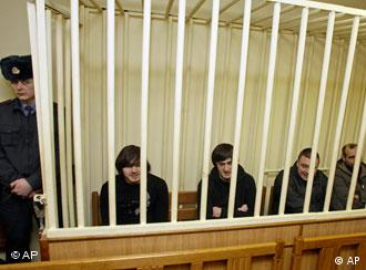 The four suspects in the murder case of Russian investigative journalist Anna Politkovskaya sit in court behind bars