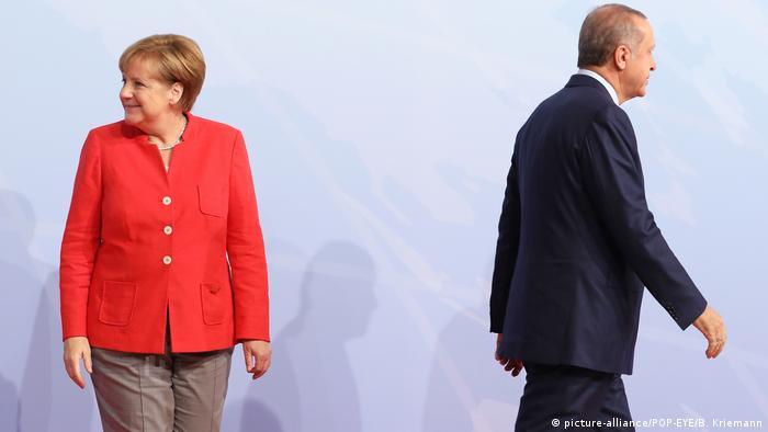 Erdogan walking away from Merkel after a press conference in Hamburg