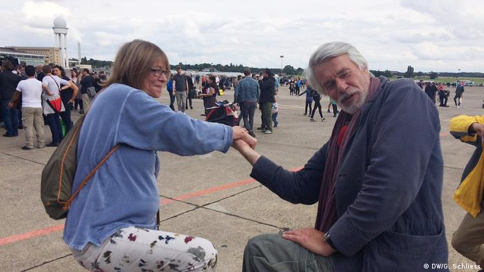 Chris Dercon arm wrestling with another person, at dance event on Tempelhof airfield