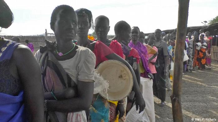 A long queue of sad-looking women waiting for food aid to be distributed