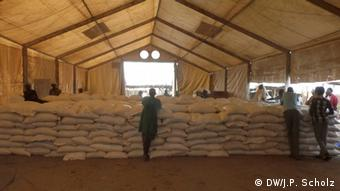 A large warehouse filled with white sacks of food aid to be distributed