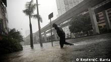 A local resident walks across a flooded street in downtown Miami as Hurricane Irma arrives at south Florida, U.S. September 10, 2017. REUTERS/Carlos Barria