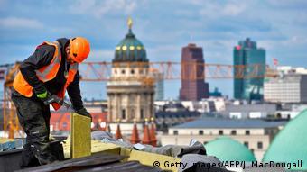 Ein Arbieter auf dem Dach des Humboldt-Forums mit Blick auf Berlins Mitte (Foto: Getty Images/AFP/J. MacDougall)