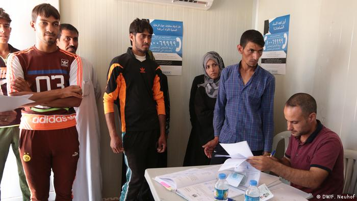 People wait for their certificates to be issued by a mobile court set up in a container in Hassansham camp