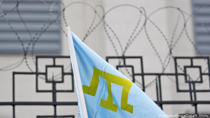 Флаг крымских татар на фоне колючей проволоки
