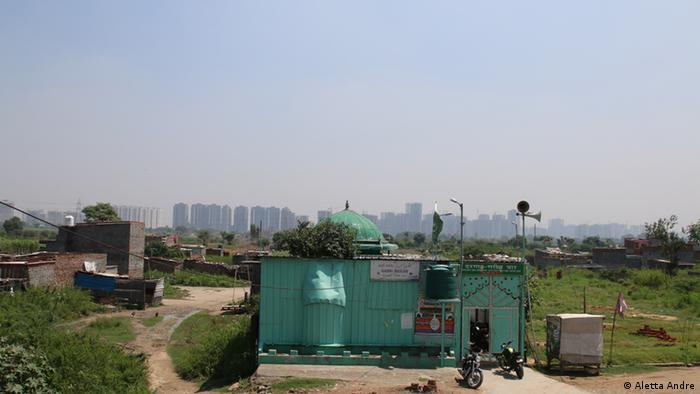 A small mosque sits on the floodplains of the Yamuna river in Delhi with highrise towers in the background.
