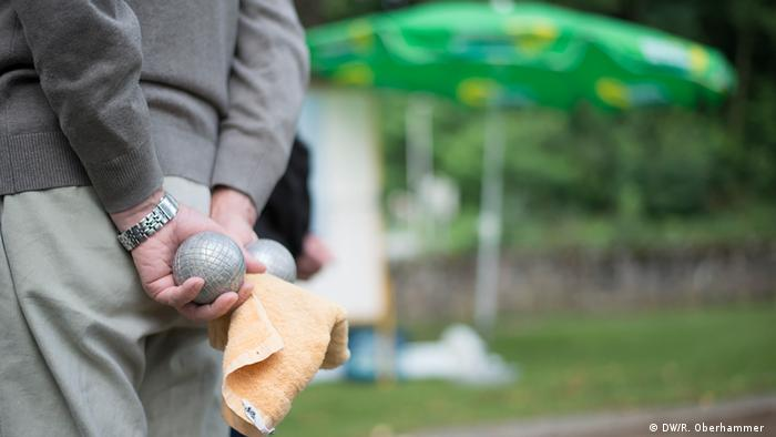 Player holding boules and a towel behind his back.