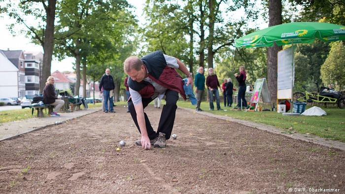 Ein Boules-Spieler bückt sich nach einer Kugel während einer Wahlkampf-Aktion von B90/Die Grünen in Osterode (Foto: DW/R. Oberhammer)