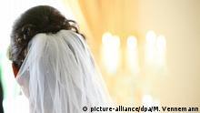 Hochzeits-Detail - der Hinterkopf einer dunkelhaarigen Braut mit Braut-Schleier im Haar vor Kerzen-Meer | Verwendung weltweit