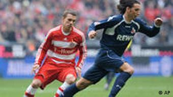 Cologne's player Pedro Tonon Geromel, right, tackles withe ball next to Munich's Lukas Podolski