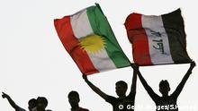 Iraqi football fans wave the Iraqi (R) and Kurdish flags as they cheer for their team during their 2014 World Cup Asian zone qualifying football match against Yemen in the northern Iraqi Kurdish city of Arbil on July 23, 2011. Iraq won 2-0. AFP PHOTO/SAFIN HAMED (Photo credit should read SAFIN HAMED/AFP/Getty Images)