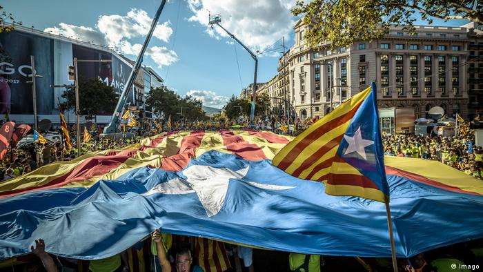Pro-independence Catalans pass a giant estelada flag through the Passeig de Gracia