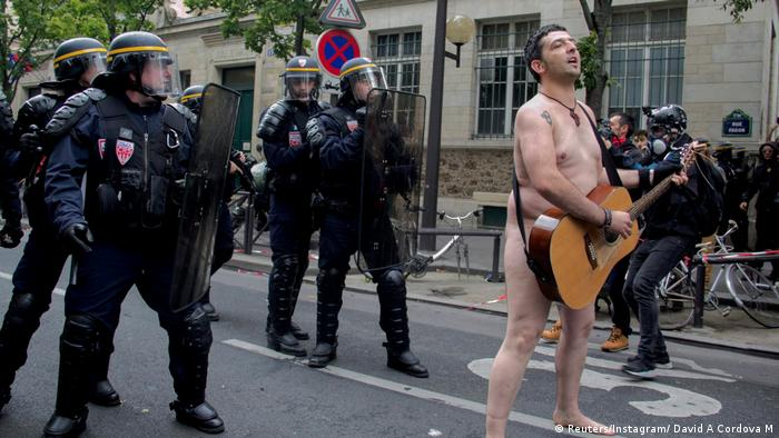 A nude protester with a guitar sings in the middle of a street as police in riot gear stand behind him (Reuters/Instagram/ David A Cordova M)