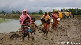 Rohingya refugees walking through mud in Bangladesh.