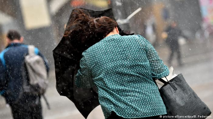 A young woman in Berlin struggles to keep her umbrella steady in the winds created by Sebastian