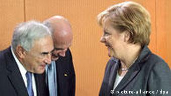 Mit einer Verbeugung begrüßen der Direktor des Internationalen Währungsfonds, Dominique Strauss-Kahn und der Generaldirektor der Welthandeslorganisation, Pascal Lamy, Bundeskanzlerin Angela Merkel (Foto: DPA)
