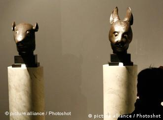A photographer takes a picture of the Chinese bronze rat head and rabbit head sculptures