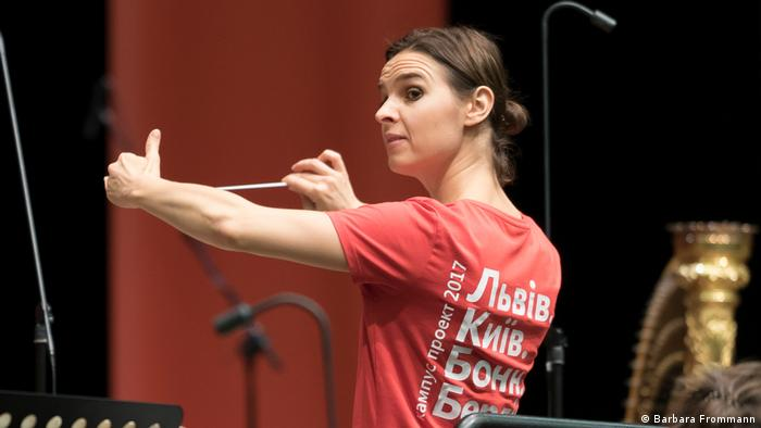 The conductor holds the baton out to her side while looking sideways