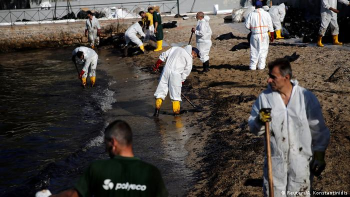 People cleaning up oil from a Greek beach
