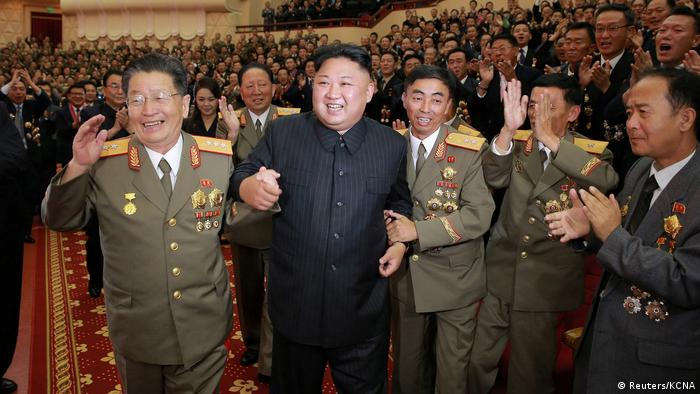 Kim Jong Un flanked by military officials