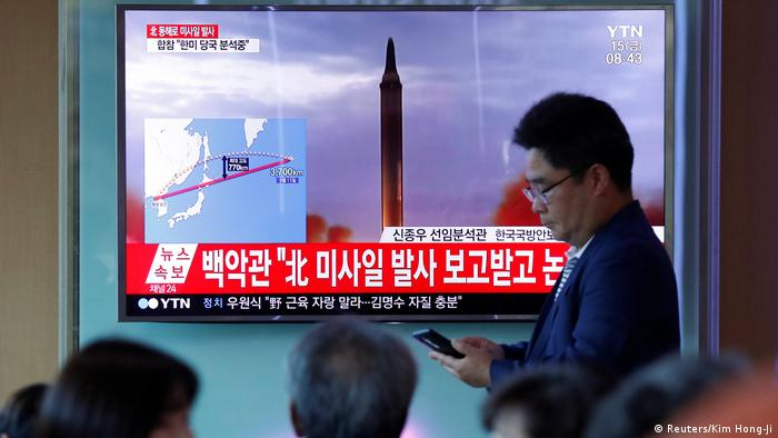 People watch a television broadcasting a news report on North Korea firing a missile that flew over Japan's northern Hokkaido