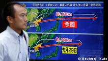 15.09.2017+++ A passerby walks past a TV screen reporting news about North Korea's missile launch in Tokyo, Japan September 15, 2017. REUTERS/Issei Kato