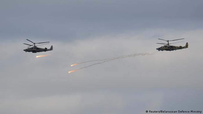 Two helicopters firing missiles