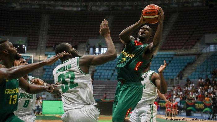 Francois Affia Ambadiang (R) of Cameroon in action against Daniel Ochefu (C) of Nigeria during the AfroBasket 2017 Quarter final round between Nigeria and Cameroon in Tunisia on September 14, 2017