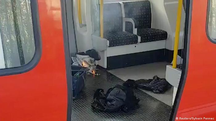 Personal belongings and a bucket with an item on fire inside it are seen on the floor of a train carriage