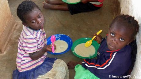 Two kids eating in a school in Malawi (imago/epd/S. Vogt)
