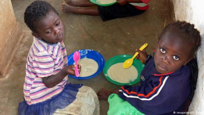 Two kids eating in a school in Malawi