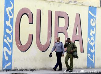 2 Cuban policemen in front of a large painted sign, reading 'Long Live Cuba'